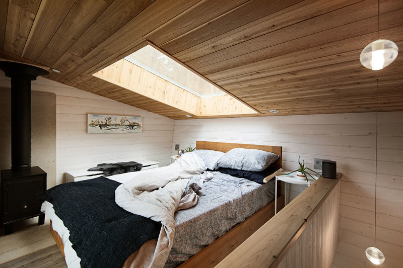 Tiny House Ideas - This modern tiny house has stairs that lead up to the lofted bedroom, that's kept bright by the use of a skylight. When it's cool outside, there's a black wood burning stove to keep the space warm. #LoftBedroom #TinyHouse #BedroomIdeas #WoodCeiling