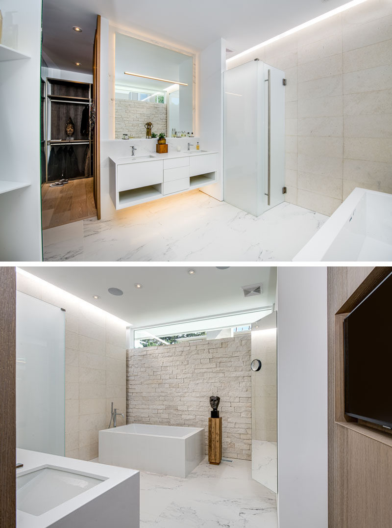 Bathroom Ideas - In this modern master bathroom, there's a floating vanity and mirror that both feature hidden lighting. Limestone walls in two styles, ledge and honed, are showcased and help to keep the bathroom bright. #BathroomIdeas #MasterBathroom #ModernBathroom