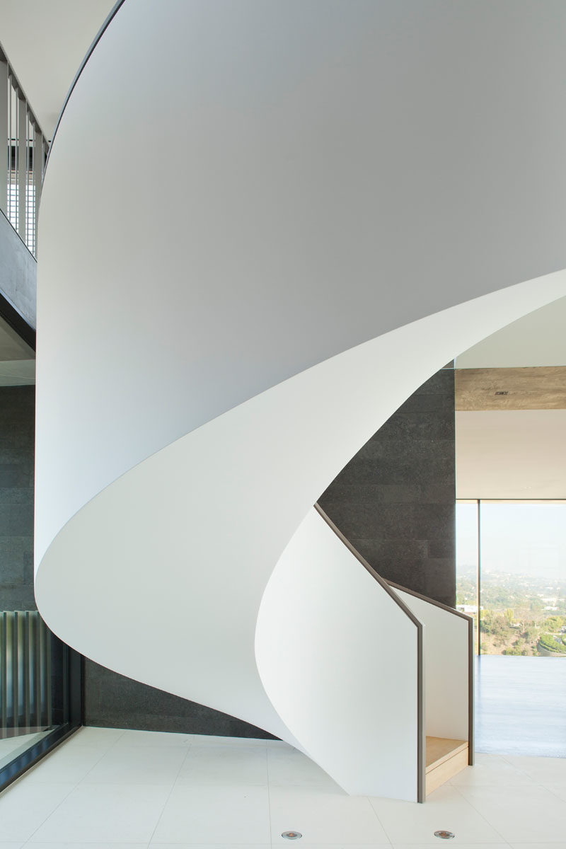 Stair Ideas - This plaster wrapped spiral staircase is a sculptural counterpoint to the bold and linear geometry of the home. #SpiralStairs #SpiralStaircase #StairIdeas #ModernStairs