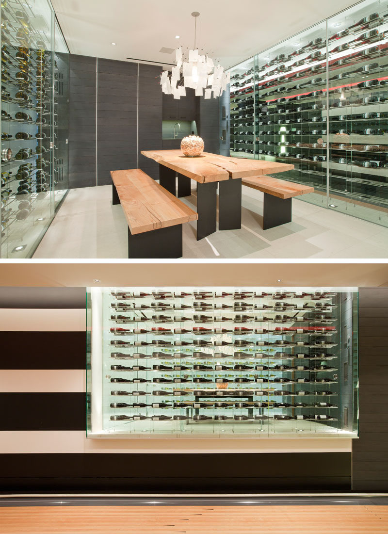 Wine Storage Ideas - This modern house has a custom-designed wine room that's furnished with a large wood and steel table and benches, while glass walls provide storage for the wine collection. #WineStorage #WineRoom