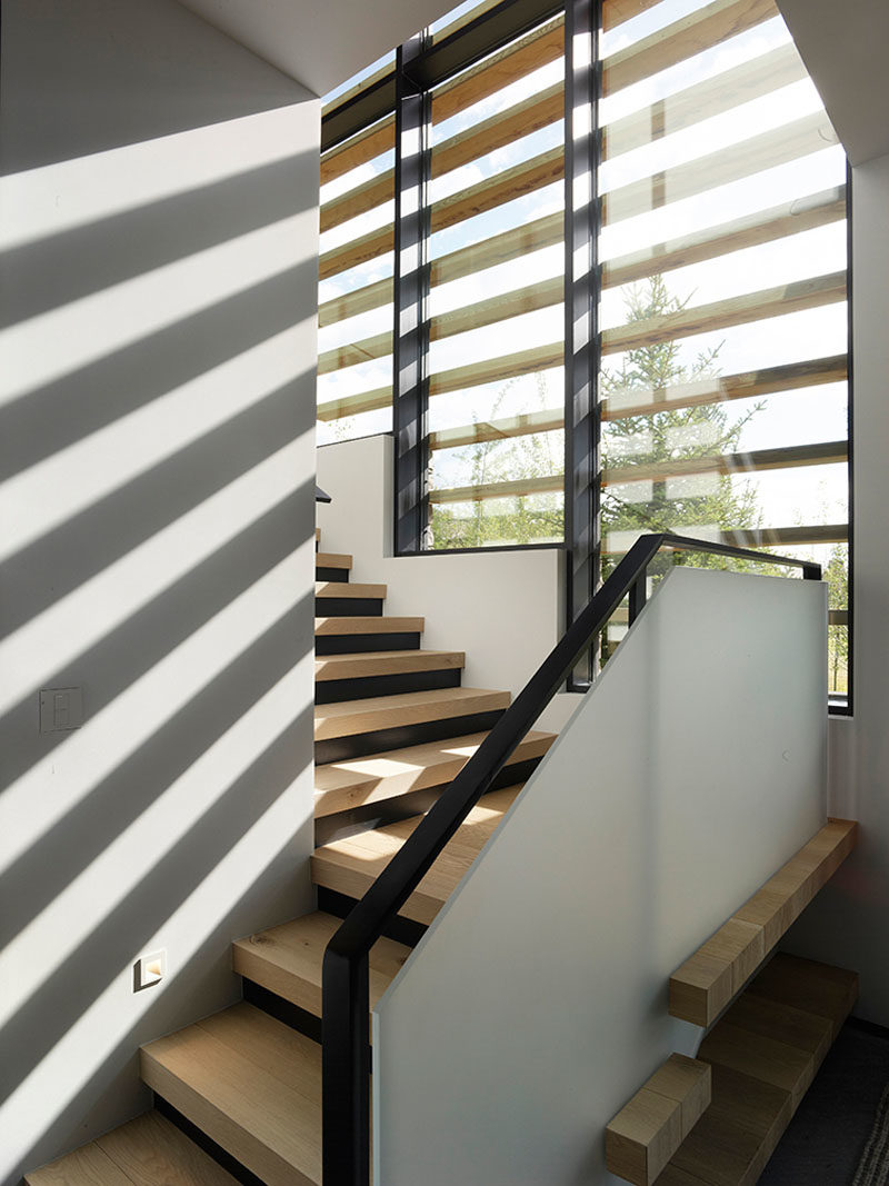 Stair Ideas - These modern wood stairs lead to the upper floor of the home, while the windows have wood accents providing an interesting shadow on the interior walls. #StairIdeas #ModernStairs #StairDesign