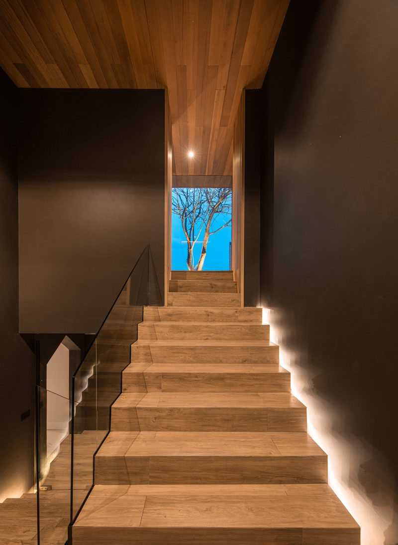 Stair Ideas - This modern rooftop house has wood stairs with hidden lighting and a glass handrail. #StairIdeas #WoodStairs #ModernStairs