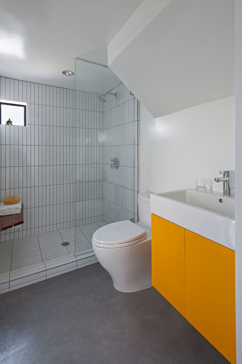 Bathroom Ideas - In this modern bathroom, a walk-in shower has vertically laid tiles, helping to create a sense of height in the small space. #BathroomIdeas #ModernBathroom #BathroomDesign