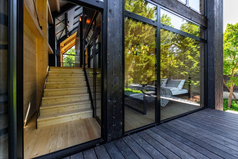 This modern resort house has black wood siding, and black framed windows. #BlackSiding #BlackWindowFrames