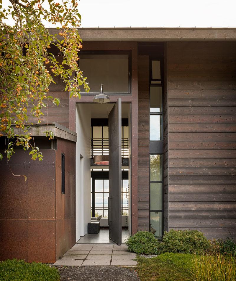 Door Ideas - This modern house features a steel front door that  pivots to reveal a tall hallway that leads to the social areas of the home. #OversizedFrontDoor #FrontDoor #SteelDoor