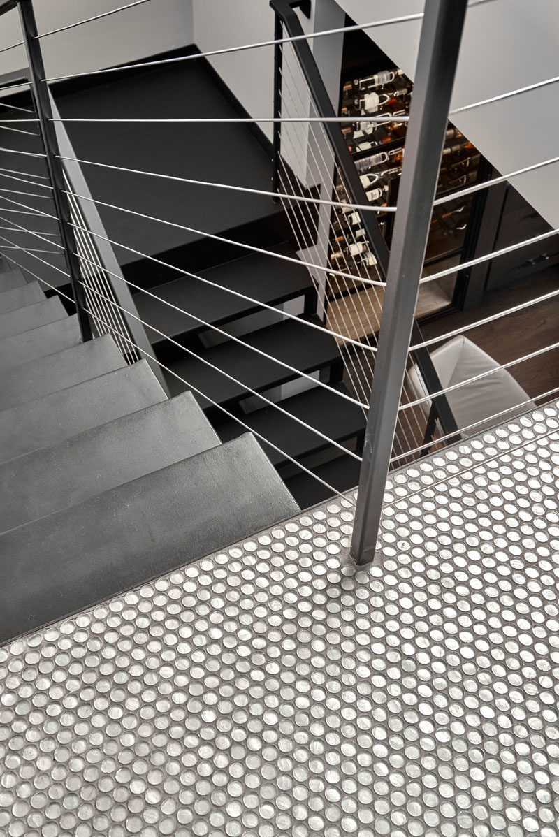 Stair Ideas - This modern blackened steel staircase leads up to the rooftop, while penny tiles add a fun touch at the top of the stairs. #StairIdeas #IndustrialStairs #ModernIndustrial #PennyTiles