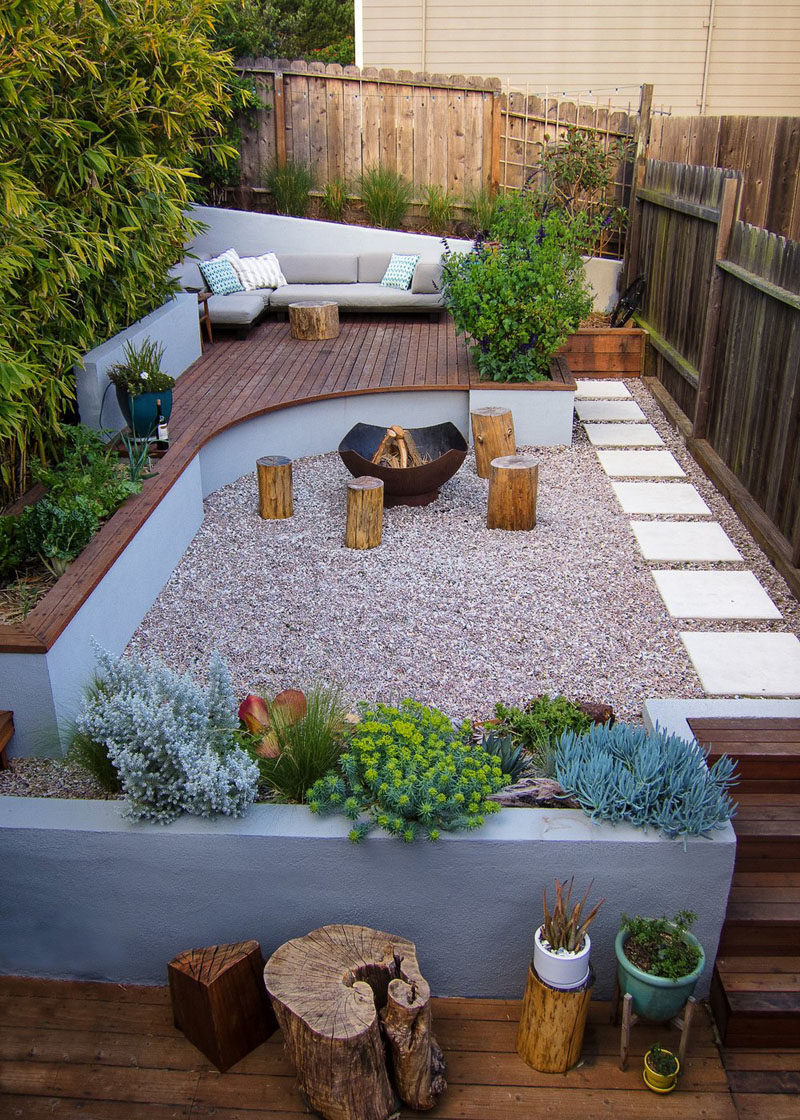 Landscaping Ideas - This modern landscaped backyard has a raised outdoor lounge deck, a wood burning firepit, succulents, bamboo, and a vegetable garden. #LandscapingIdeas #GardenIdeas #PlantIdeas #ModernYard #ModernBackyard #TieredYard