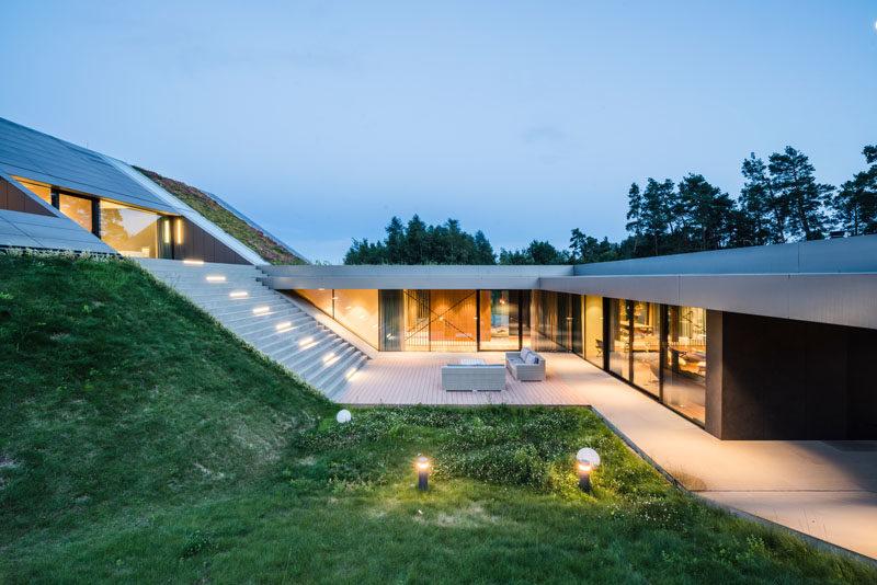 Architecture Ideas - This modern has been built into the hillside, integrating with the surrounding landscape, and creating a closeness to nature. #ArchitectureIdeas #GreenRoof #ModernHouse #ModernArchitecture #GlassWalls