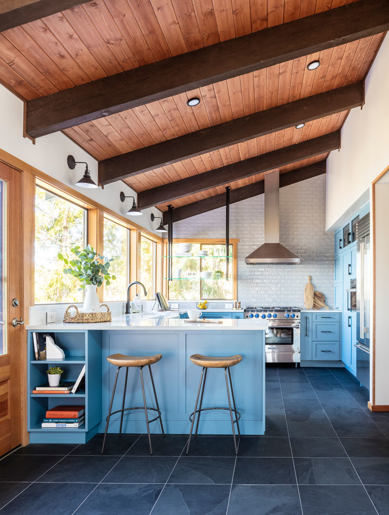 Kitchen Ideas - This modern kitchen features unexpected blue cabinets have been combined natural medium woods found throughout the home, an uneven light gray backsplash tile acts as a subtle yet striking backdrop for the kitchen, and black slate flooring and black metal accents throughout added depth and interest. #KitchenIdeas #ModernKitchen #BlueKitchen #KitchenDesign