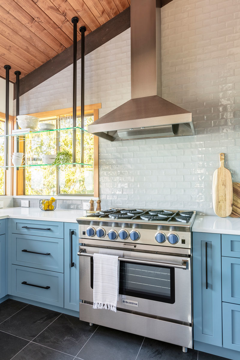 Kitchen Ideas - On each side of the stove, there's a spice/utensil pullout, keeping everything in arms reach when cooking, while a custom designed suspended shelf system allows the homeowners to display beautiful dishware and still keep their view.  #KitchenIdeas #BlueKitchen #BlueCabinets #Stove #KitchenDesign