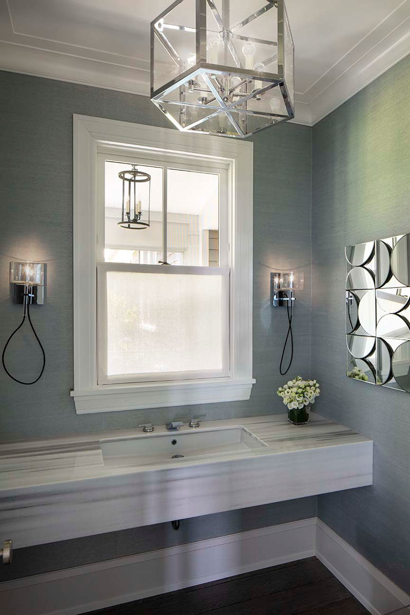 Bathroom Ideas - In this contemporary bathroom, textured grey wallpaper covers the walls, while chrome accents have been added in the form of lighting and wall art. #BathroomIdeas #BathroomDesign #GreyBathroom