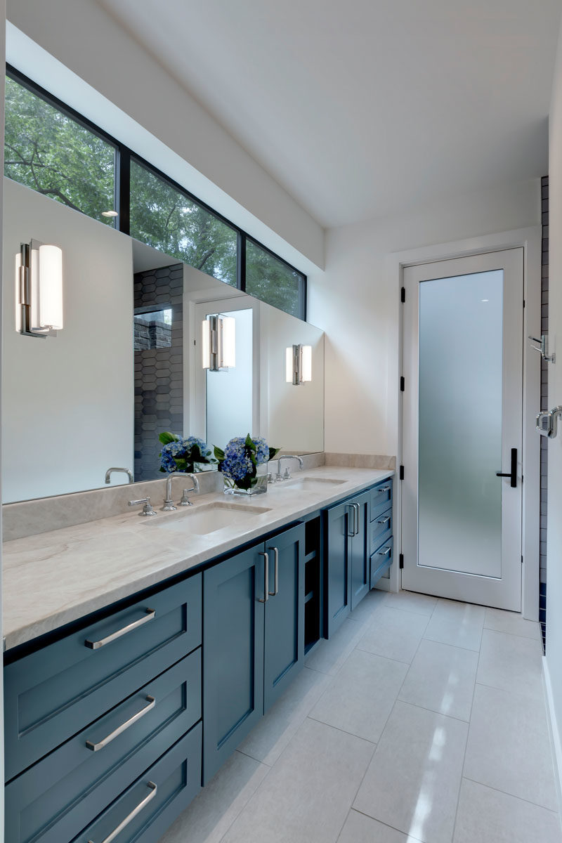 Bathroom Ideas - In this modern bathroom, clerestory windows and a frosted glass door add natural light to space, while a large vanity provides plenty of storage space. #BathroomIdeas #BathroomDesign #Modernbathroom
