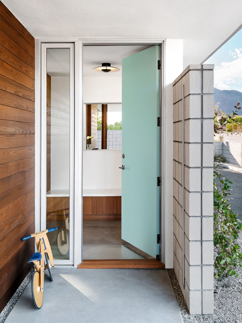 Front Door Ideas - A light blue front door welcomes visitors to this mid-century modern inspired house, that features polished concrete floors throughout. #BlueFrontDoor #FrontDoorIdeas #MidCenturyModern