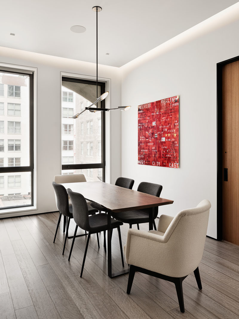 Dining Room Ideas - In this modern dining room, a minimalist pendant light hangs above the dining table, while red artwork adds a pop of color to the open interior. #DiningRoomIdeas #InteriorDesign #ModernDiningRoom