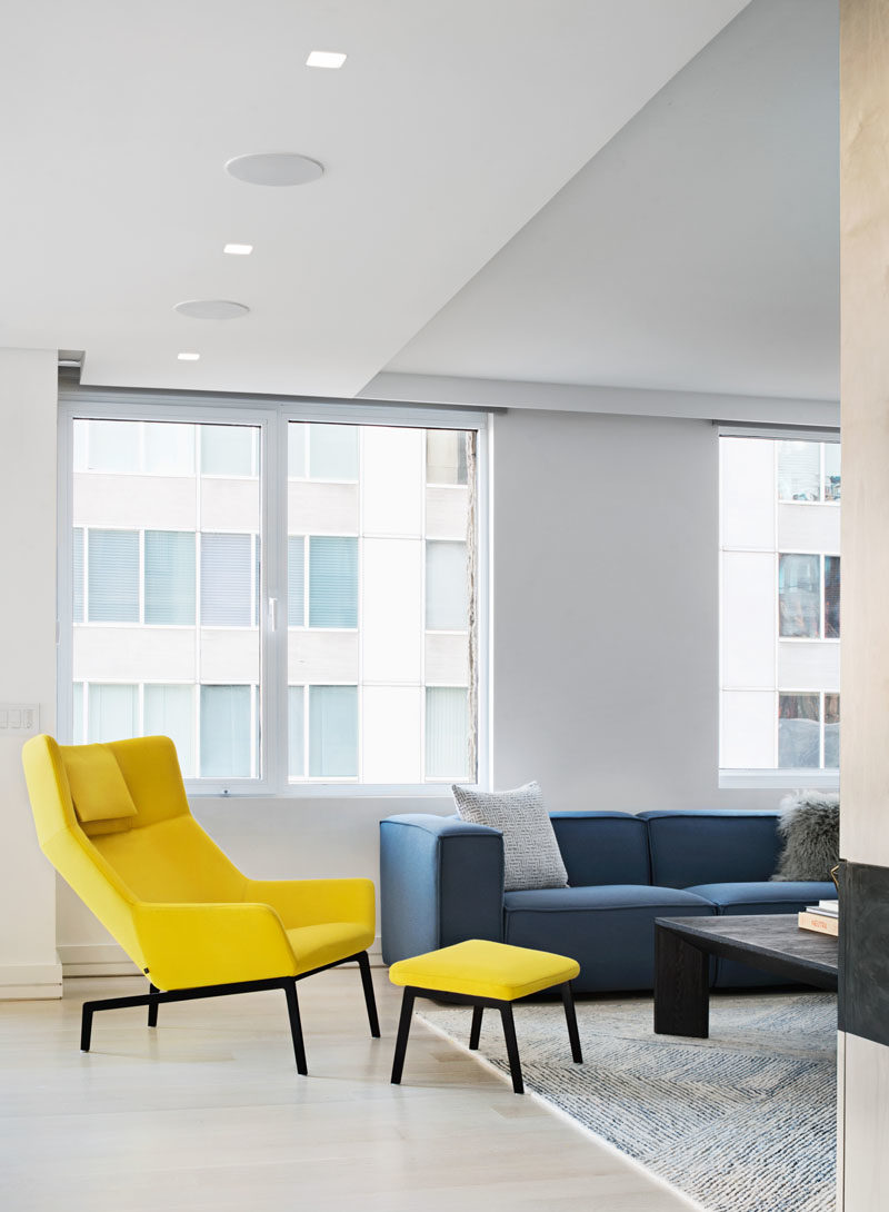 A yellow armchair and ottoman add color, brightness, and a sense of fun to this modern apartment interior. #InteriorDesign #ModernInterior
