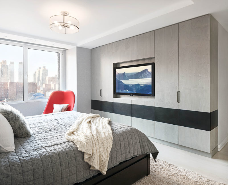 Bedroom Ideas - In this modern master bedroom, the television has been set back into the cabinets, and a blackened steel inlay provides contrast to the grey-washed birch veneer millwork. #ModernBedroom #CabinetIdeas #BedroomIdeas #Wardrobe #Closet