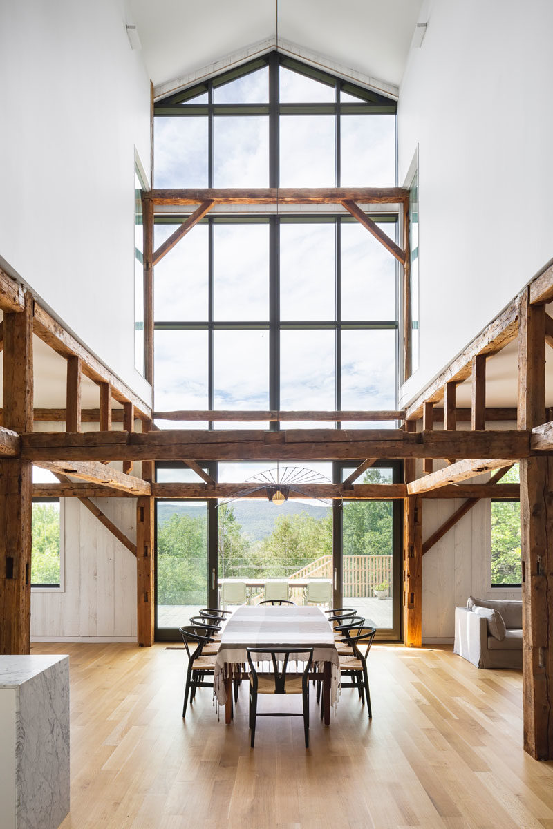 Dining Ideas - Inside this modern barn, the 30 foot ceiling height creates a space that's both open and welcoming, with the old wood elements proudly displayed. Windows flood the dining area with an abundance of natural light. #DiningRroom #Windows #ModernBarn