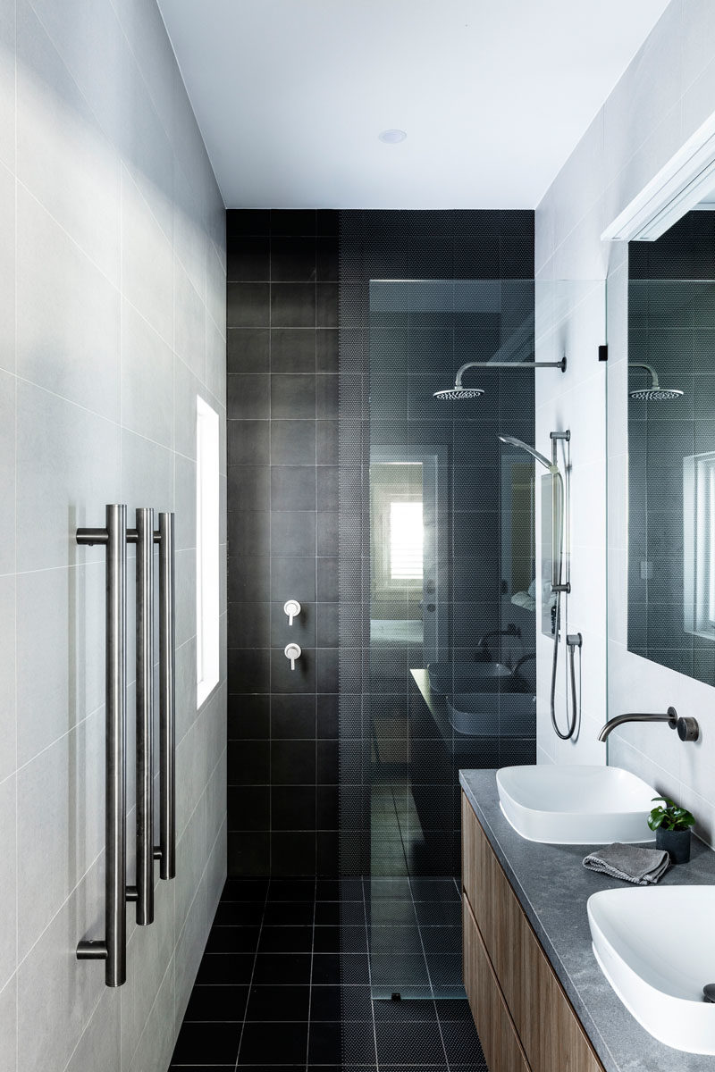 Bathroom Ideas - This modern bathroom has square black tiles that travel from the shower onto the floor, while square grey tiles cover the remaining walls. #BathroomIdeas #BlackTiles #ModernBathroom
