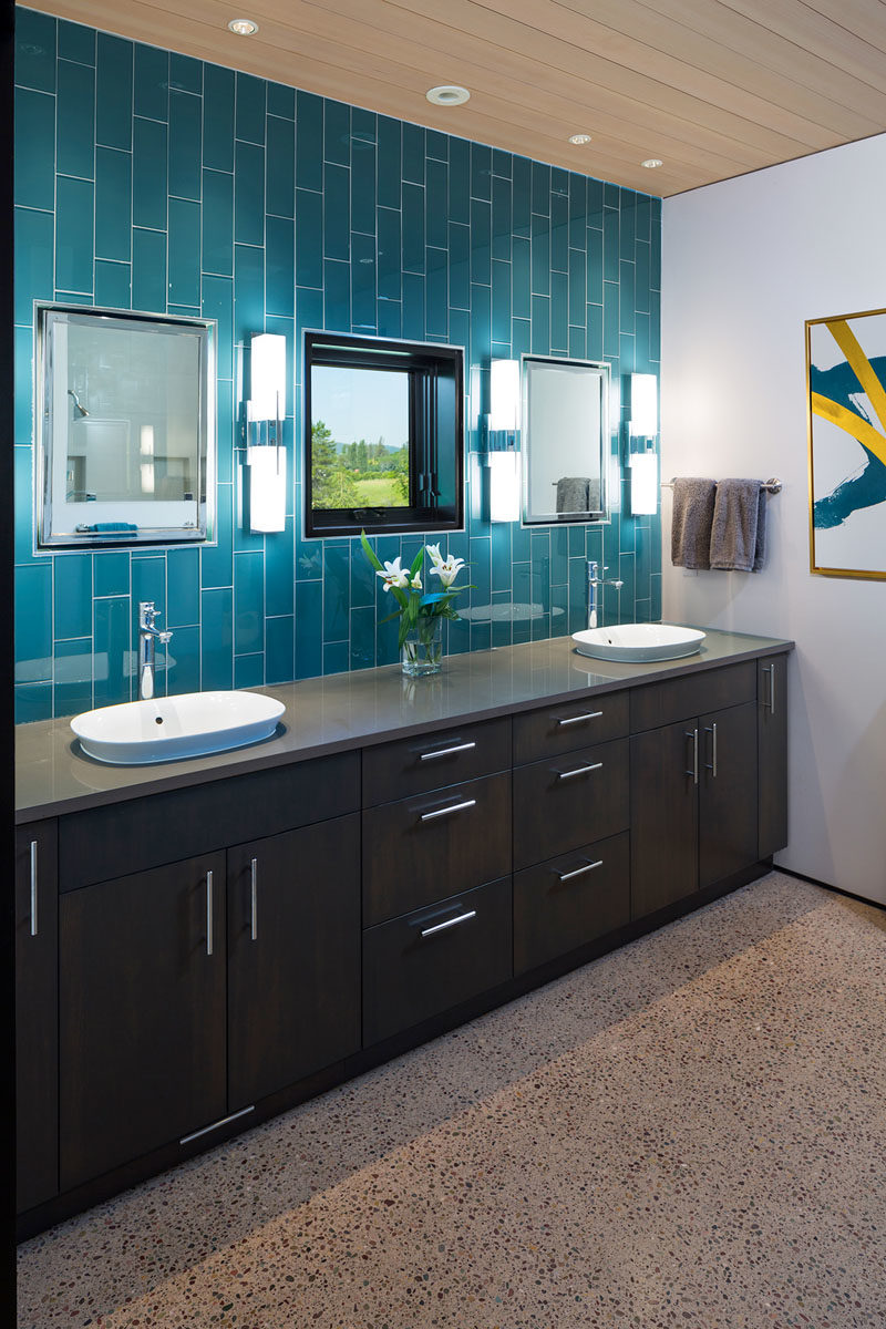 Bathroom Ideas - In this modern bathroom, blue tiles laid vertically draw attention to the height of the room. A wall-to-wall dark wood vanity provides plenty of space for two, while the mirrors are positioned on either side of the mirror. #BathroomIdeas #ModernBathroom #BlueTiles #WoodCeiling