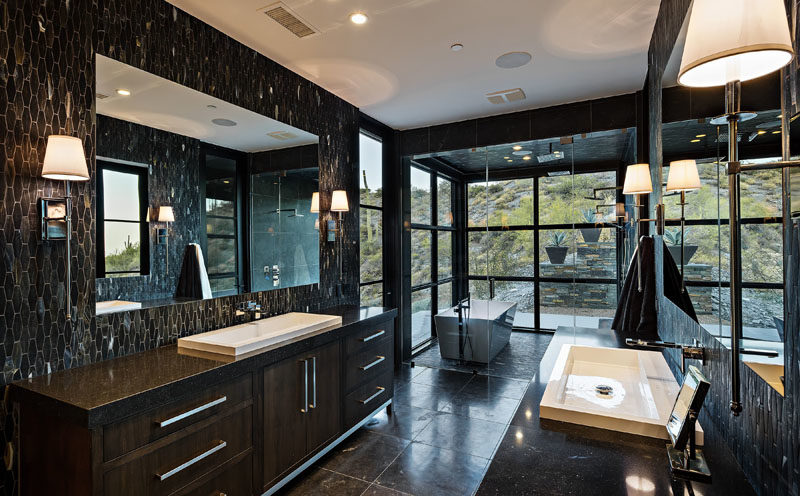 Bathroom Ideas - In this modern bathroom, black tiles create a dramatic appearance, while the freestanding bathtub and dual shower is located within a glass room, making it feel like you're outside. #ModernBathoom #BathroomIdeas #BathroomDesign