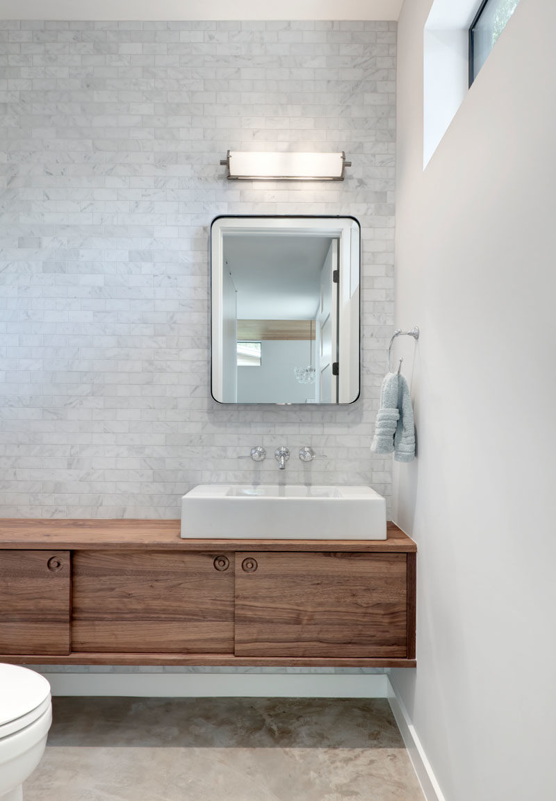 Bathroom Ideas - In this modern bathroom, light grey tiles cover the wall, and a simple floating wood vanity adds a natural element. #BathroomIdeas #ModernBathroom #BathroomDesign