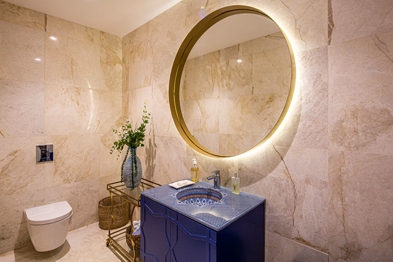 Bathroom Ideas - In this modern bathroom, a blue vanity has a decorative top, while the large round mirror is backlit, and a small side table adds a place to display a vase. #BathroomIdeas #ModernBathroom #BathroomDesign