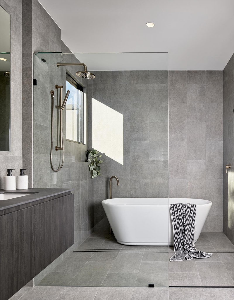 Bathroom Ideas - In this modern bathroom, grey tiles cover the walls, while a seamless glass partition separates the shower and bathtub from the rest of the room. #BathroomIdeas #BathroomDesign #GreyBathroom