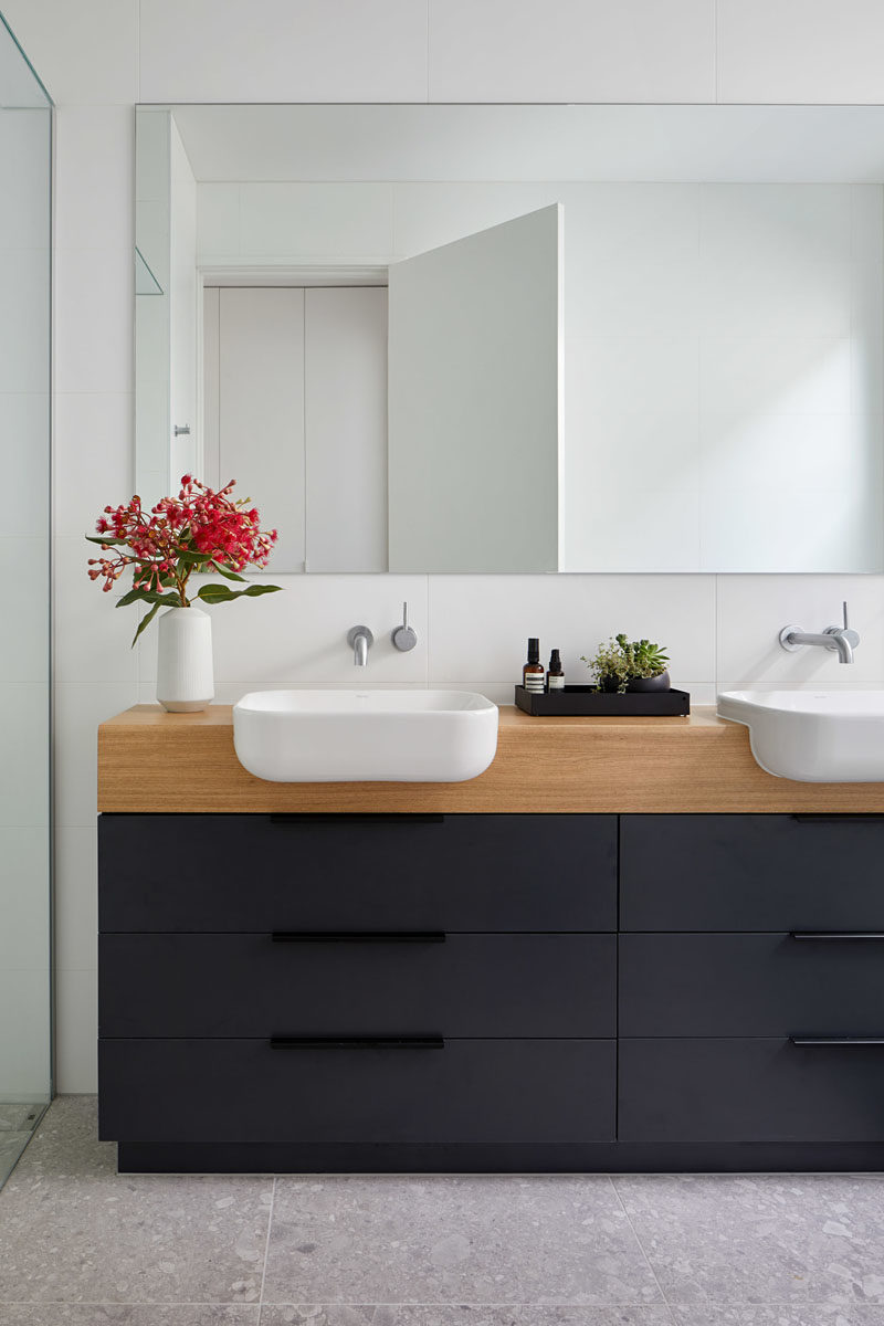 Bathroom Ideas - In this modern bathroom, a black and wood vanity contrasts the white walls, while the mirror reflects light throughout the space. #BathroomIdeas #ModernBathroom #BlackVanity