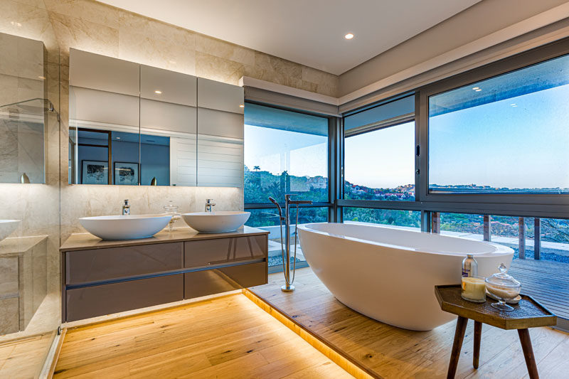 Bathroom Ideas - In this master bathroom, the freestanding bathtub is raised up on a platform, while hidden lighting creates a soft glow and a calming atmosphere. #ModernBathroom #BathroomIdeas #BathroomDesign