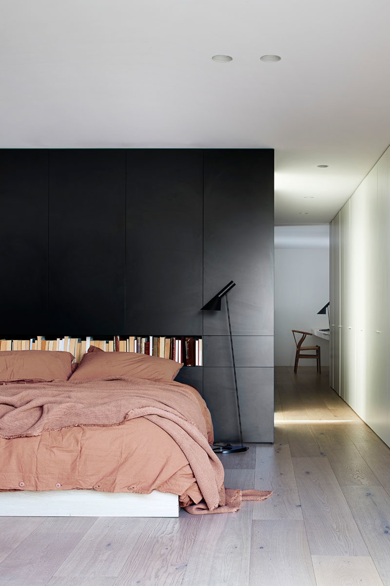 Bedroom Ideas - In this modern master bedroom, a black wall creates a bold backdrop for the bed, and a built-in shelf adds room for storing books. #MasterBedroom #BedroomDesign #BlackAccentWall #BlackWall #BedroomIdeas