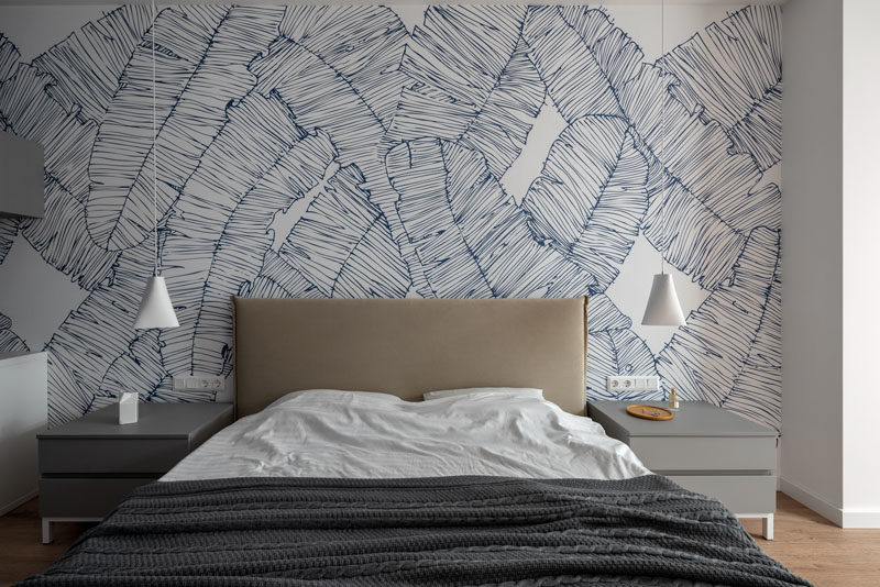 Bedroom Ideas - In this modern master bedroom, a leafy mural covers the wall behind the bed, while two minimalist white pendant lights hang from the ceiling. #BedroomIdeas #ModernBedroom #BedroomMural