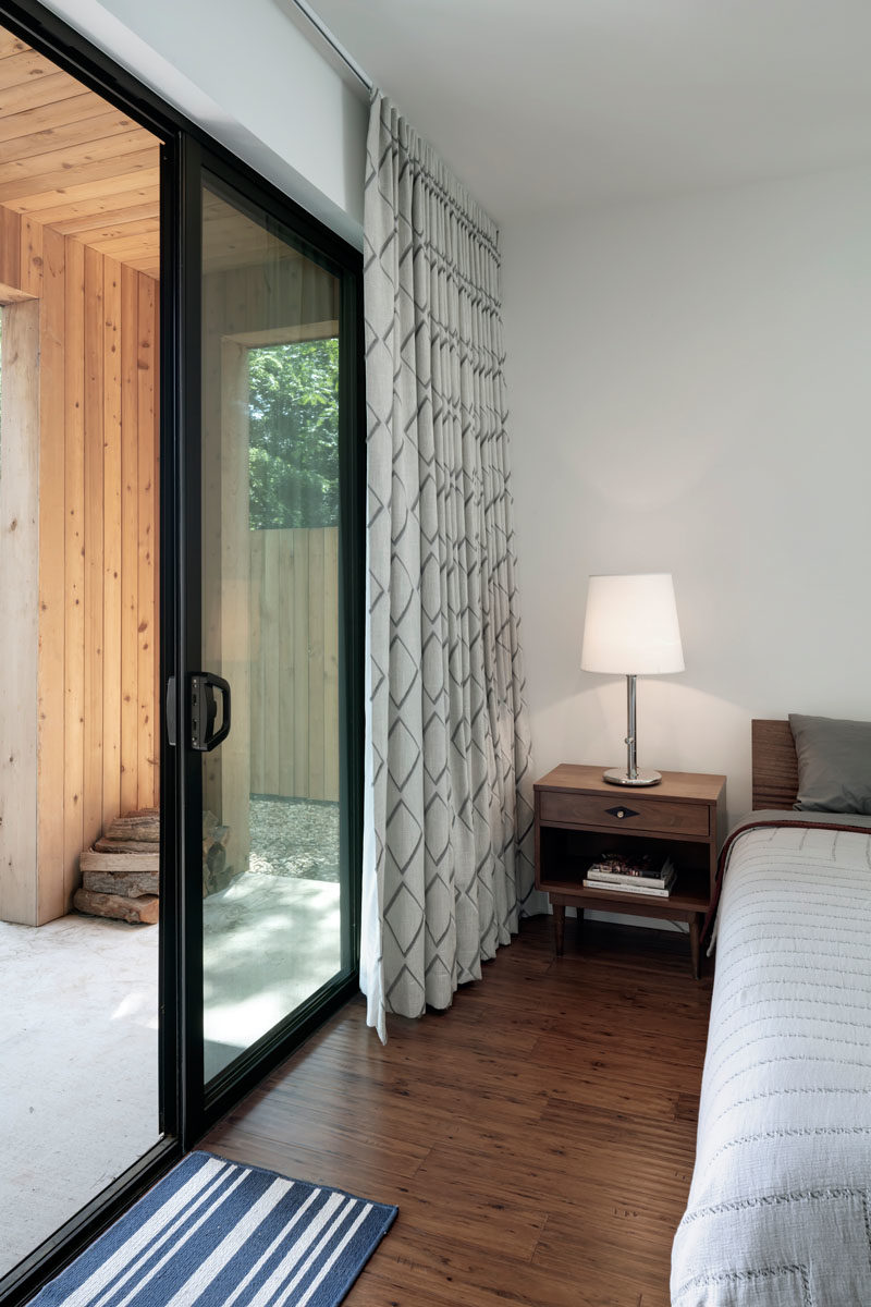 A small covered porch provides this bedroom with a private outdoor space, while inside, the furnishings have been kept minimal for a relaxed atmosphere. #Bedroom #SlidingDoor