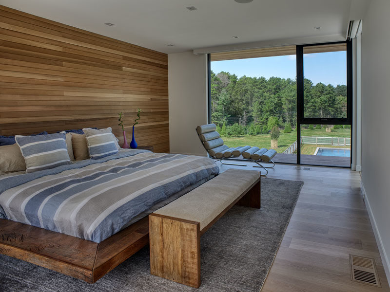 Bedroom Ideas - This modern bedroom has a wood accent wall that complements the wood found throughout the house, and the bed frame. A large window provides a view of the yard and the trees in the distance. #BedroomIdeas #MOdernBedroom #WoodAccentWall