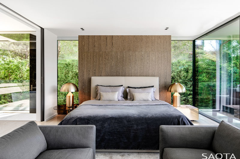 Bedroom Ideas - This modern bedroom has been designed with floor-to-ceiling glass walls and a wood accent wall. #GlassWalls #ModernBedroom #BedroomIdeas