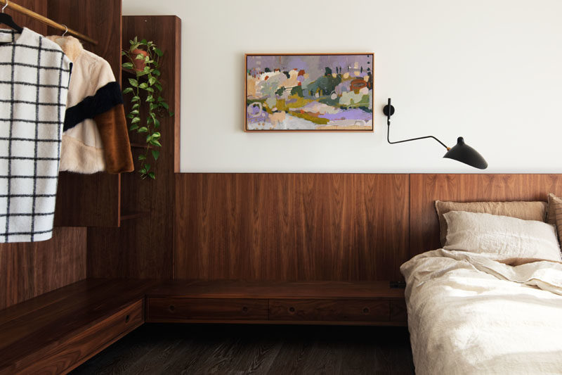 Bedroom Ideas - This modern bedroom features dark wood that has been used to create a headboard that travels along the wall to become an open closet. #BedroomDesign #BedroomIdeas #ModernBedroom #OpenCloset #WoodHeadboard