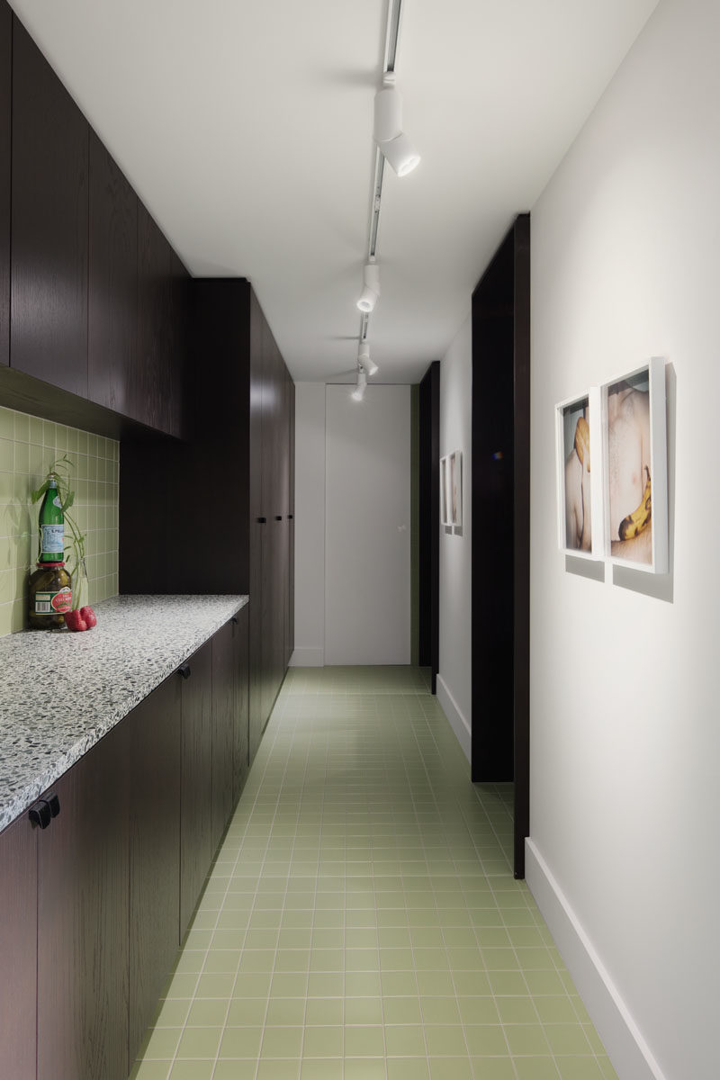 Pantry Ideas - A door in the kitchen leads to a butlers pantry that features the same dark cabinets and pastel green tiles, keeping a cohesive appearance. #ButlersPantry #Pantry #GreenTiles #DarkCabinets