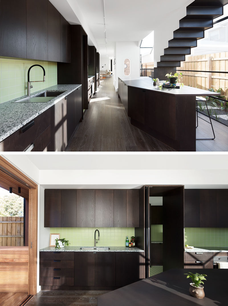 Kitchen Ideas - This modern kitchen features dark stained minimalist wood cabinets that have been brightened up with the use of a pastel green tile. #DarkCabinets #KitchenDesign #ModernKitchen #GreenTiles