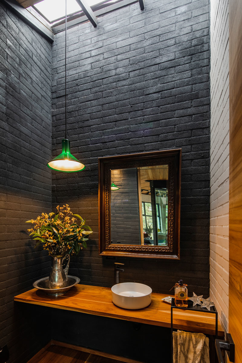 Bathroom Ideas - This small bathroom has dark grey brick walls, while a skylight floods the room with natural light, helping to keep it bright. #BathroomIdeas #BlackBathroom #Skylight #SmallBathroom #BlackBrick