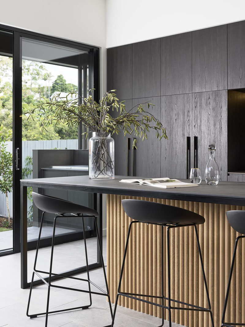Kitchen Ideas - In this modern kitchen, minimalist dark cabinets line the wall, and an island with room for bar seating, features a wood accent. #KitchenIdeas #DarkKitchen #ModernKitchen #KitchenDesign