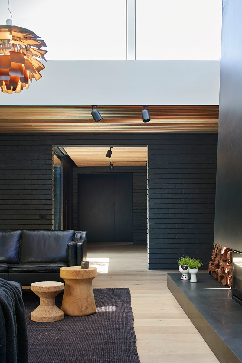 Living Room Ideas - In this modern living room, a large black steel fireplace commands attention, while a single pendant light anchors the rug and furniture in the open space. #ModernLivingRoom #LivingRoomIdeas #BlackLivingRoom #BlackFireplace
