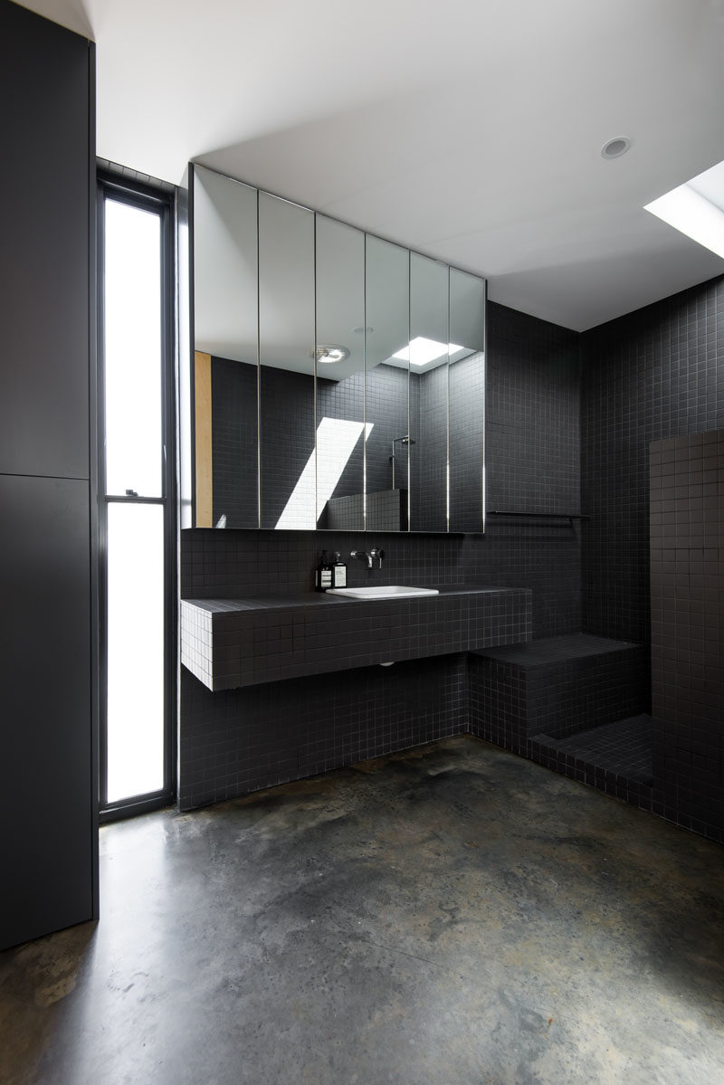 Bathroom Ideas - This modern bathroom features a fully tiled ensuite bathroom, that showcases small black tiles, an open shower with a skylight, a frosted window, and a mirror with hidden shelving. #BathroomIdeas #BlackBathroom #ModernBathroom