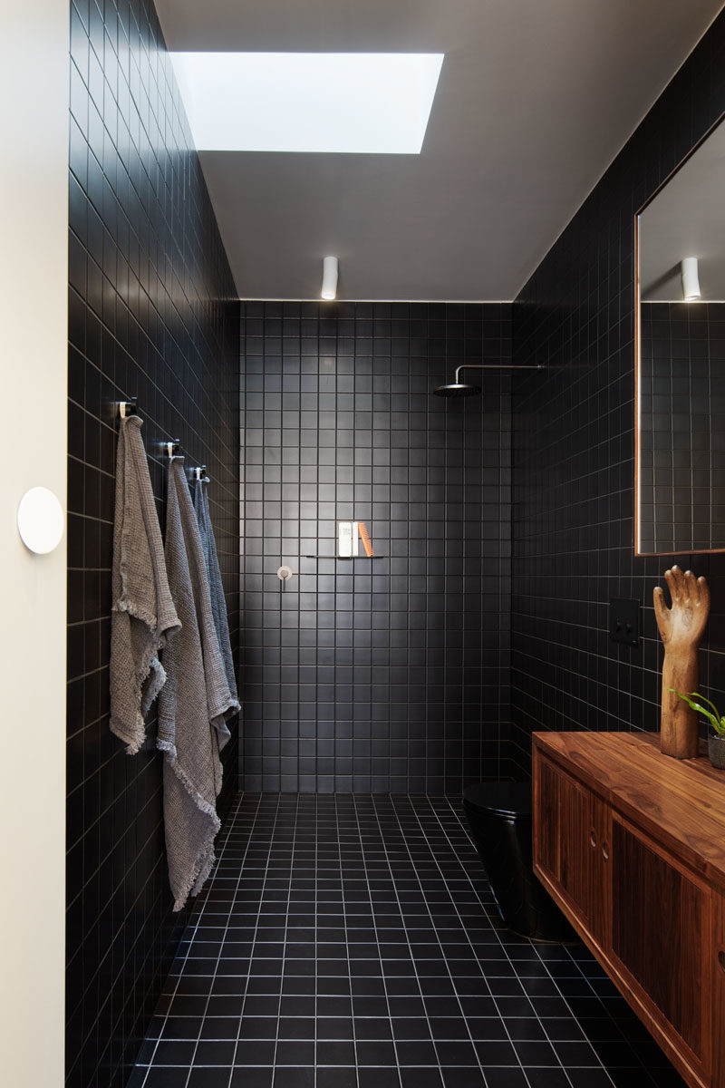Black Bathroom - This modern bathroom features square black tiles that cover the walls and floor. A skylight helps to keep the room bright. #BathroomIdeas #BlackBathroom #ModernBathroom