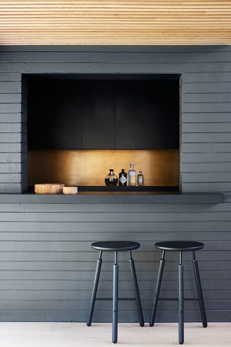 Home Bar Ideas - This modern black home bar features a metallic accent, creating a luxurious feeling. #HomeBar #ModernBar #BarDesign
