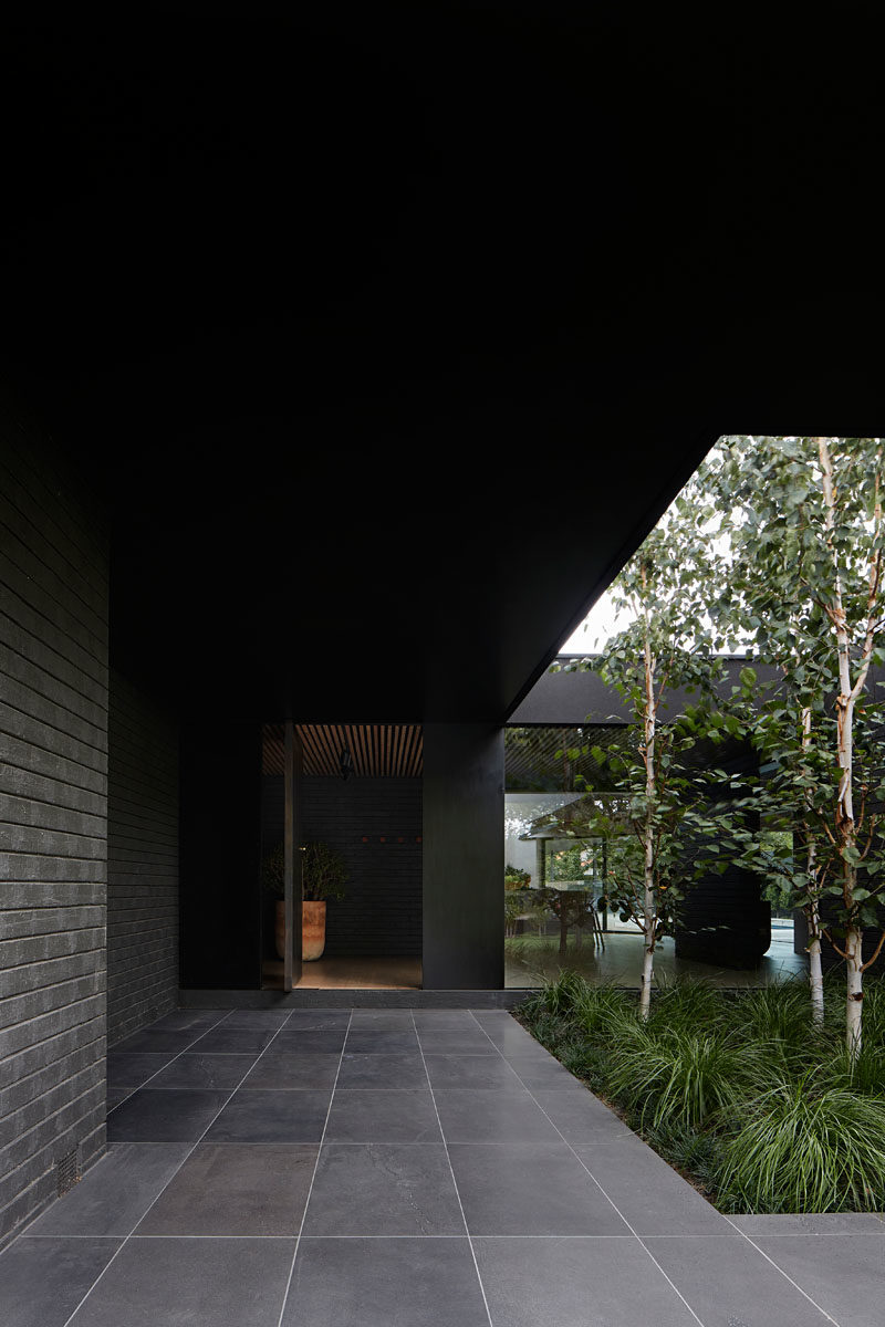 On arrival to this modern black house, the entry is defined by an oversized eave that's been punctured to allow soft landscaping adjacent the entrance, as well as provide increased light into the interior of the home. #ModernHouse #BlackHouse #HouseDesign #Landscaping