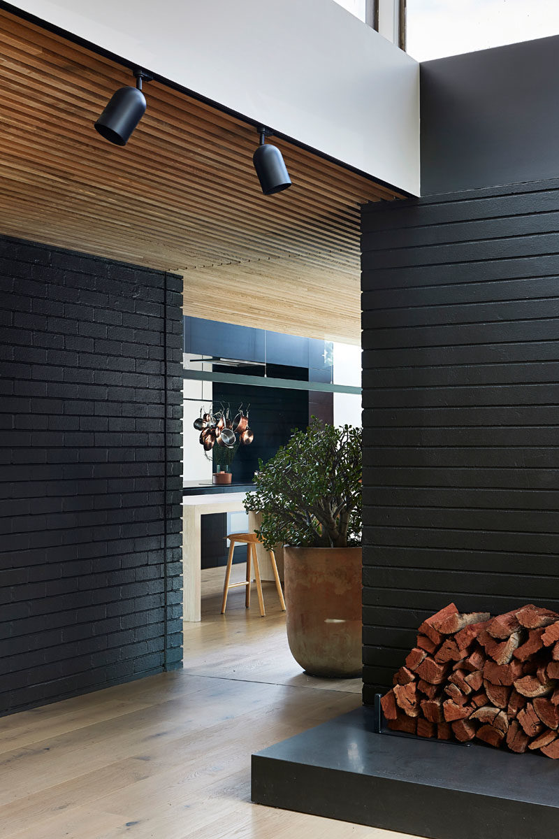 The exterior materials, like black brick, have been carried through to the inside of this house, creating a cohesive look and modern interior. #ModernInteriorDesign #ModernArchitecture #BlackBrick