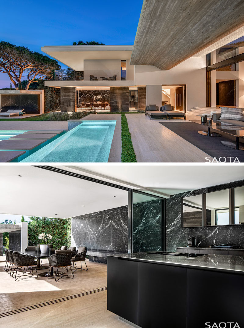 This modern house has terraces can also be accessed via the dining room and kitchen, that are both stepped down from the foyer, and feature dark marble walls. #Terraces #ModernHouse #DiningRoom #Kitchen