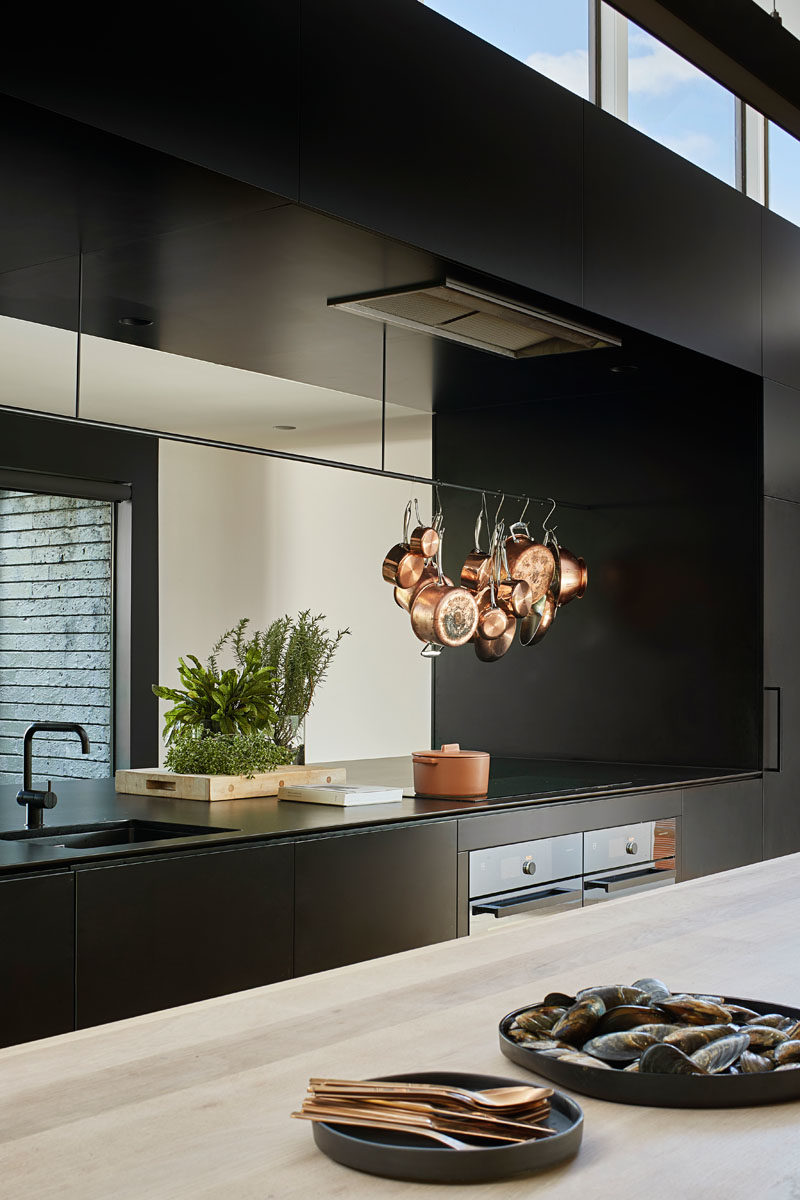 Kitchen Ideas - In this modern kitchen, minimalist black cabinets line the wall, and a large island provides ample counter space and a place for sitting. A void in the cabinets allows for connectivity between the kitchen and the pantry, that's located behind the cabinets. #KitchenIdeas #BlackKitchen #KitchenDesign #ModernKitchen