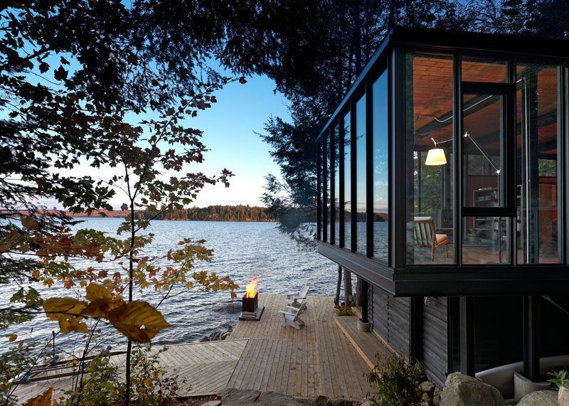 Building Arts Architects has designed a new modern boat house on the shores of Kawagama Lake in Ontario, Canada, that includes dry slip boat storage via marine railway, and a 452 square foot (42 sqm) dwelling space. #ModernArchitecture #BoatHouse #ModernBoatHouse #LakeHouse
