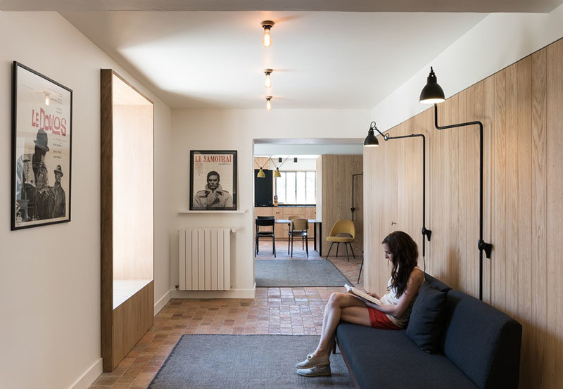 Window Seat Ideas - This modern hallway has a partially built-in window seat, that's lined with wood and views of the garden outside. #WindowSeat #WindowSeatIdeas #Seating