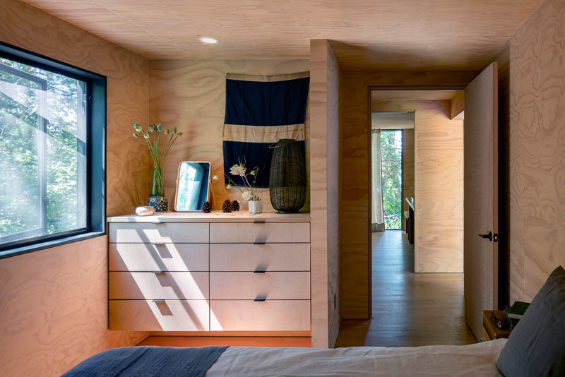 In this wood-lined bedroom, a picture window provides natural light and an uninterrupted view of the trees. #BedroomIdeas #BuiltInStorage #Windows #Bedroom